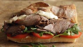 Het koken procédé die de sandwich van het braadstukrundvlees met arugula van de tomatenkomkommer maken stock videobeelden
