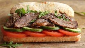 Het koken procédé die de sandwich van het braadstukrundvlees met de salade van de tomatenkomkommer maken stock video