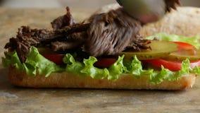 Het koken procédé die de sandwich van het braadstukrundvlees met tomaat en salade maken