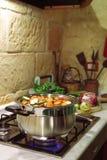 Het koken in rustieke keuken Stock Afbeelding