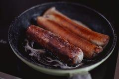 Het koken van één of andere heerlijke Duitse braadworst bij de keuken stock foto