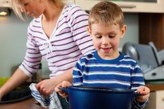 Het koken van de familie in keuken stock afbeeldingen