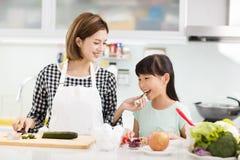 Het koken van de moeder en van de dochter in de keuken royalty-vrije stock afbeeldingen