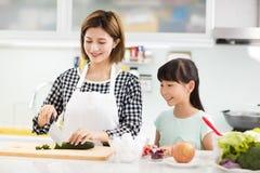 Het koken van de moeder en van de dochter in de keuken stock afbeeldingen