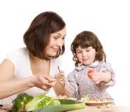 Het koken van de moeder en van de dochter bij de keuken stock fotografie