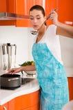 Het koken van de vrouw in de keuken, proevende soep Stock Foto