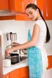 Het koken van de vrouw in de keuken, proevende soep Stock Foto's