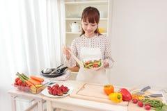 Het koken van de vrouw in keuken Stock Foto