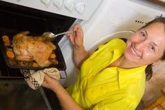 Het koken van de vrouw kip in oven royalty-vrije stock fotografie