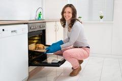 Het koken van de vrouw kip in oven stock fotografie