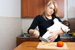 Het koken van de vrouw met baby Stock Afbeeldingen