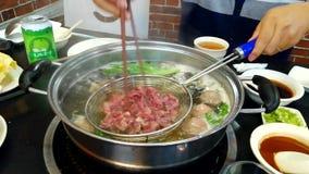 Het koken van een echte hete de pottenschotel van Chaoshan met gesneden rundvlees stock footage