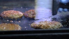 Het koken van een hamburger, een pasteitje of een lapje vlees Voor een heet fornuis, een vlees van kokgebraden gerechten in een p stock footage