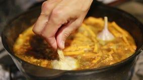 Het koken van een pilau, shef voegt knoflook in een gietijzerketel toe stock video