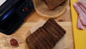 Het koken van een sandwich in de keuken hoogste mening van de reeks voor het maken van een sandwich Toostbrood, bacon, saus, sand stock videobeelden