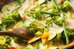 Het koken van een vegetarische maaltijd in een wok, room het bespatten op groenten stock foto's