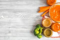 Het koken van fijngestampte wortelen voor baby op houten hoogste mening als achtergrond Stock Afbeelding