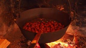 Het koken van geroosterde kastanjes in de pan op brand in een de herfstdag