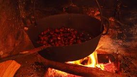 Het koken van geroosterde kastanjes in de pan op brand in een de herfstdag stock video