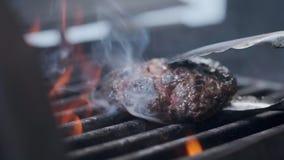 Het koken van hamburger Rundvlees of varkensvleeskotelet die op net roosteren Kokmens die een hamburgerpasteitje op de grill voor stock video