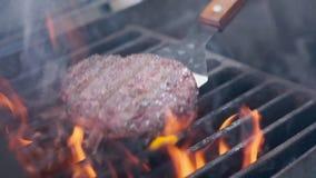 Het koken van hamburger Rundvlees of varkensvleeskotelet die op net roosteren Kokmens die een hamburgerpasteitje op de grill voor stock footage