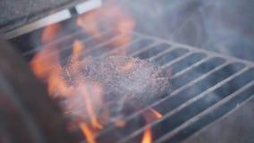 Het koken van hamburger Rundvlees of varkensvleeskotelet die op net roosteren Kokmens die een hamburgerpasteitje op de grill voor stock videobeelden
