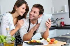 Het koken van het paar met hulp van Internet Stock Foto's
