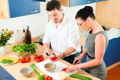 Het koken van het paar samen in keuken stock foto's