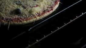 Het koken van Italiaanse pizza in elektrische convectieoven Het plaatsen van pizza op een bakselblad binnen heet kooktoestel pizz stock videobeelden