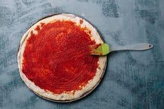 Het koken van Italiaanse pizza met tomaten, kip, olijven op houten achtergrond Tomatensaus op het deeg door de hand van de vrouw stock afbeeldingen