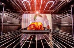 Het koken van kip in de oven Stock Foto