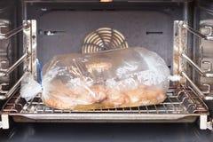 Het koken van kip in de oven op de ovenzak royalty-vrije stock foto's