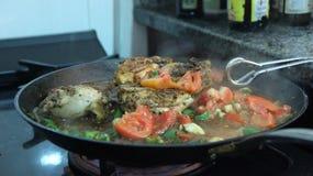 Het koken van kip in saus Stock Afbeeldingen