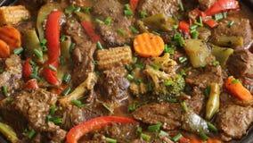 Het koken van proces bradend vlees met groentenclose-up op een panrecept stock video