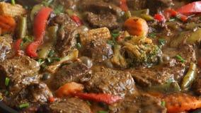 Het koken van proces bradend vlees met groentenclose-up op een panrecept stock videobeelden