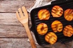 Het koken van Rijpe perziken op een grill panclose-up De horizontale bovenkant wedijvert Royalty-vrije Stock Foto's