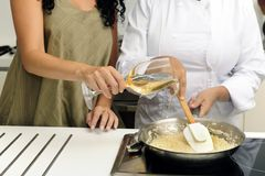 Het koken van risotto gietende wijn stock foto's