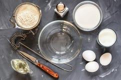Het koken van Russische schotelspannekoeken: eieren, melk, bloem, boter, zout stock afbeelding
