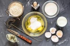 Het koken van Russische schotelspannekoeken: eieren, melk, bloem, boter, zout stock fotografie