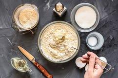 Het koken van Russische schotelspannekoeken: eieren, melk, bloem, boter, zout Hand het bewegen deeg royalty-vrije stock foto's