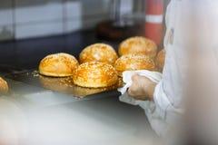 Het koken van sesambroodjes en chef-kok dient de keuken in royalty-vrije stock foto's