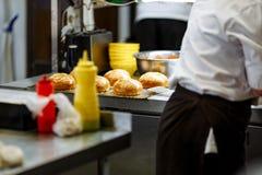 Het koken van sesambroodjes en chef-kok dient de keuken in stock afbeelding