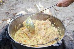 Het koken van smakelijk pilau in aard Kokend pilau in grote ketel op brand bij picknick Kokend pilau in een pot op de brand dicht stock foto's