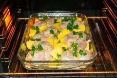 Het koken van vleeskwartels in de oven Gehele kwartelsmarinovani in kruiden met uien en mosterd Versier met verse aardappels en p royalty-vrije stock afbeeldingen