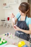 Het koken, voedsel en het bakken concept - chef-kok die met banketbakkerijzak room het vullen drukken aan macaronsshells bij pati Royalty-vrije Stock Afbeelding