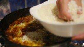 Het kokende pilau, shef voegt witte rijst in gietijzerketel toe stock videobeelden