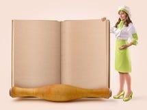 Het kokmeisje toont een pagina van een oud boek Royalty-vrije Stock Afbeelding