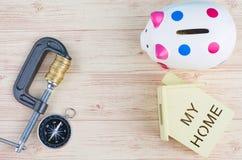 Het kompas, de huisreplica, het spaarvarken en de muntstukken drukten strak in een g-Klem over houten achtergrond royalty-vrije stock fotografie