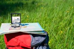 Het kompas en de kaart liggen op rugzak Stock Foto