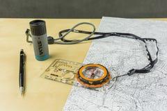 Het kompas en het potlood zijn nuttig wanneer het planning van een wandelingsreis op een topografische kaart stock afbeeldingen